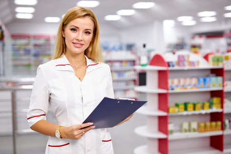 portrait of good-looking blonde pleasant female pharmacist writing on clipboard at pharmacy, make notes, wearing white medical gown. check list of drugs 版權商用圖片