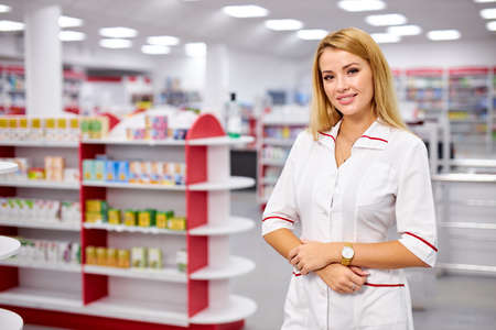 portrait of beautiful young woman pharmacist in uniform at modern drugstore, attractive diligent druggist at work, ready to help customers