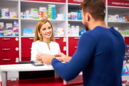 young beautiful caucasian pharmacist is working with customer in modern drugstore, serve the client, wearing white medical gown 版權商用圖片