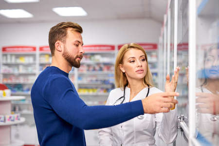 young female pharmacist helping sick male customer choosing prescription drugs from the shelf, shopping at drugstore, taking advice from professional chemist. consumerism, friendly staff concept