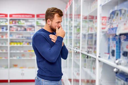 young caucasian adult man is suffering from sore throat, need some medications in pharmacy