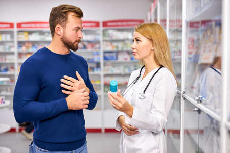 young caucasian helpful female druggist dealing with a male customer, explaining a prescription to ill patient, client