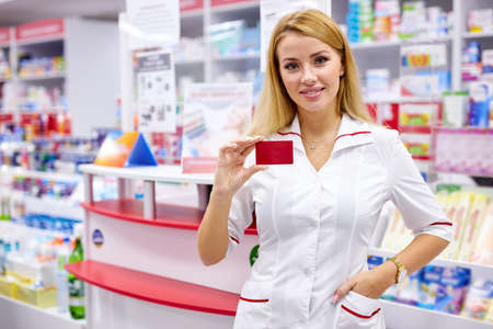 portrait of good-looking drugstore worker holding props card of pharmacy in hands, pleasant affable druggist welcomes clients and customers 版權商用圖片