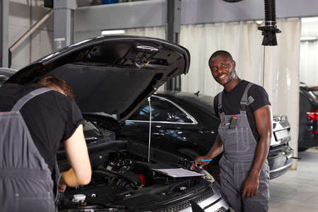 multi-ethnic team of african and caucasian men working in auto service together, friendly men in uniform repair the car hood