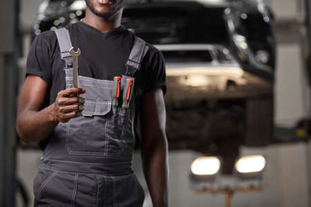 cropped black afro auto mechnic holding tool for repairing a car, wearing uniform