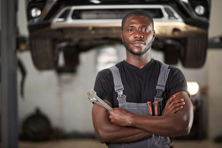 professional black auto mechanic looking at camera, handsome black guy in uniform is keen on repairing car. automobile in the background Reklamní fotografie