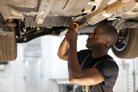 young male car mechanic in uniform checking car in automobile service with lifted vehicle, handsome hardworking guy working under car condition on lifter. automotive car repair concept