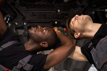 two interracial car mechanics in uniform checking car in automobile service with lifted vehicle, african and caucasian men repair a car together 版權商用圖片