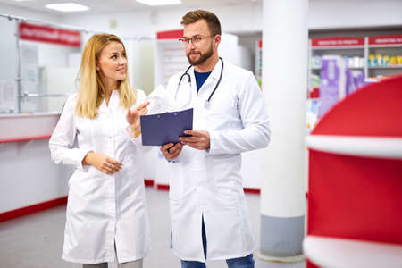 team of young caucasian chemists or druggists discussing medicines, check medical indications, in white medical gowns, at work place