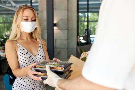 adorable woman customer take her order in restaurant during coronavirus, waiter staff of cafe give food in container wearing protective gloves, woman is in medical mask