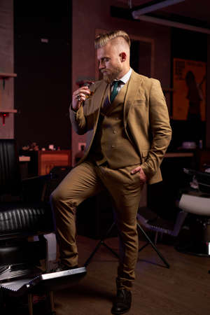 good-looking male in suit drinking alcohol, he holds glass of beverage in hands, posing alone