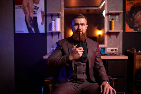 professional hair stylist is ready to cut your hair or beard, male in suit at work place, posing in dark room