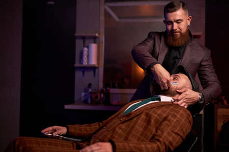 beauty shop for men concept. professional hairdresser shaving a beard to rich clients in a barbershop, brutal haircuts