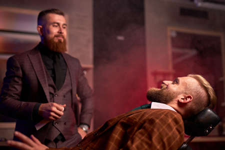 portrait of confident caucasian barber male and his client in salon, professional hair stylist going to cut bearded guy in suit, sitting on chair 免版税图像