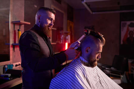 confident caucasian barber mster cuts hair and beard of men in the barbershop, professional hairdresser makes hairstyle for a young man, he works with clipper machine