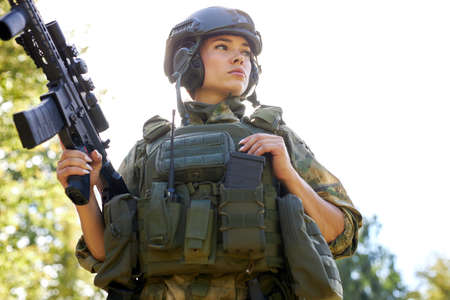 young caucasian military woman holds a gun in her hand in nature, she is going to hunt, hunting in forest is a hobby. game with weapons Stock Photo