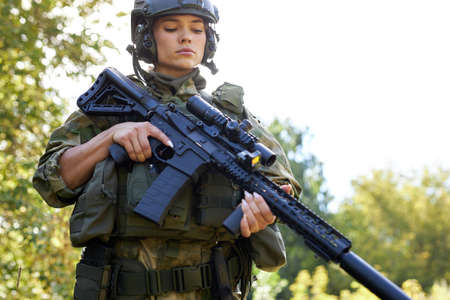 young caucasian military woman is checking rifle in the forest before shooting, alone in nature, female soldier Stock Photo