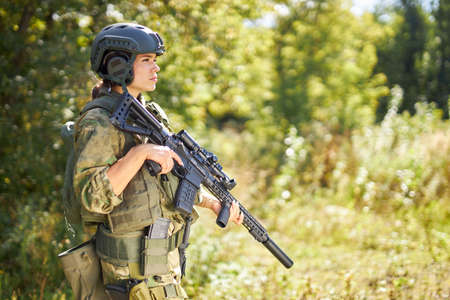 strong brave female army soldier with rifle machine gun standing in the forest, she is ready to shoot at enemy, firearm outdoor shooting range