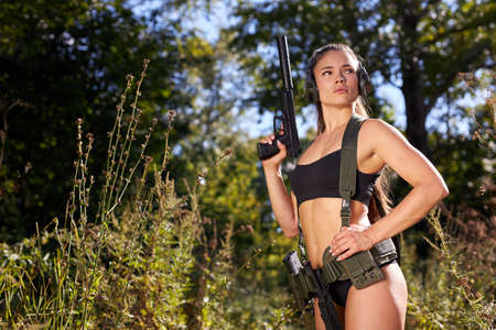 half-naked female hunter in top and camouflage waiting for opportunities to shoot using weapon or rifle, hunting concept