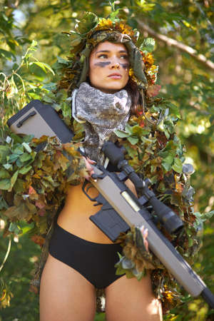 half-naked female hunter in top and camouflage waiting for opportunities to shoot using weapon or rifle, hunting concept Banque d'images