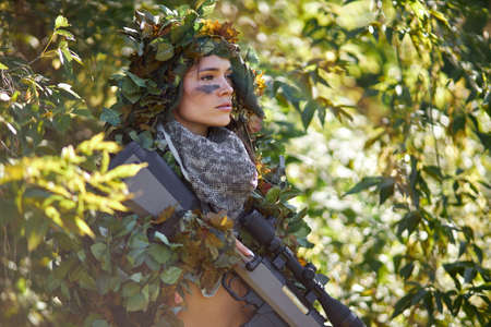 young caucasian clever woman deer hunter in green uniform with disguise and rifle in the forest, she is keen on hunting in nature, strong and fearless