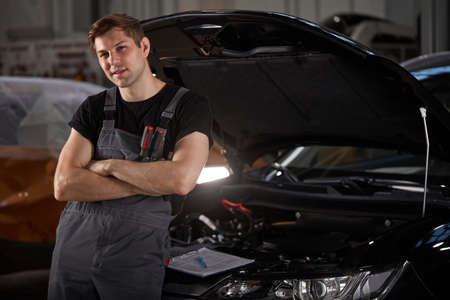 portrait of confident caucasian mechanic in uniform posing at camera in auto service, young male likes his work connected with repair of cars Standard-Bild