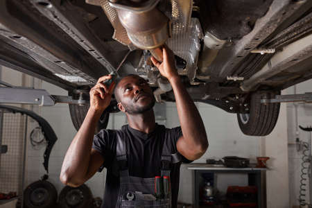 handsome african male repairing bottom of car, check and examine all details. hardworking man in uniform at work