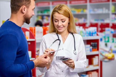 caucasian friendly pharmacist has a nice conversation with a client, helps to find a medication, ask about symptoms and what is he suffering from Foto de archivo