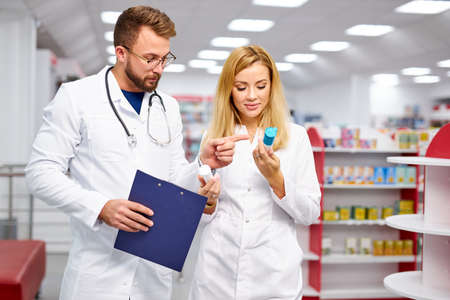 two young professional druggists colleagues fulfilling a prescription holding medication in hand, checking the script Banque d'images