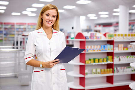 portrait of good-looking blonde pleasant female pharmacist writing on clipboard at pharmacy, make notes, wearing white medical gown. check list of drugs