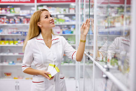 young good-looking woman pharmacist searching for medication on pharmacy shelves, examine and check assortment of drugs in pharmacy Stok Fotoğraf