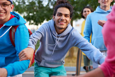 portrait of cheerful caucasian teenager boys outdoors, young guys in colourful casual wear run forward, smile. happy team Foto de archivo