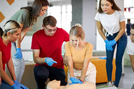 group of young caucasian people learning how to safe a life sitting together on lesson, discussing all techniques, using mannequin to show an example