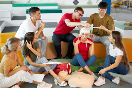 people at class of giving first aid, learn bandaging the head, sit isolated in room, discuss technique