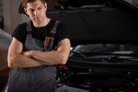 portrait of sad auto mechanic guy standing next to car looking down, wearing uniform. in garage Stockfoto