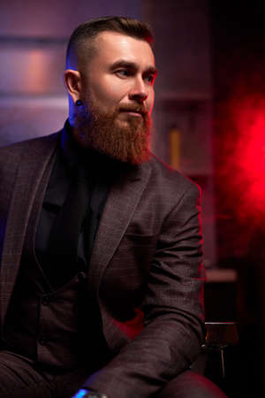 young caucasian handsome bearded man in suit sitting on couch in a dark smoky room, he is elegant and attractive, male is lost in thought. dramatic evening, dark shadows and wealth