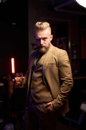 young caucasian bearded business man drinking glass of whiskey indoors in dark room, wearing formal suit