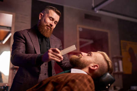 hairstyling process. barber cutting beard of caucasian male with the use of scissors, client sits in an armchair Archivio Fotografico - 159143938