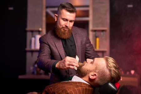 young caucasian handsome man on chair of barber having procedure of shaving, get beauty procedures in barber shop salon 版權商用圖片