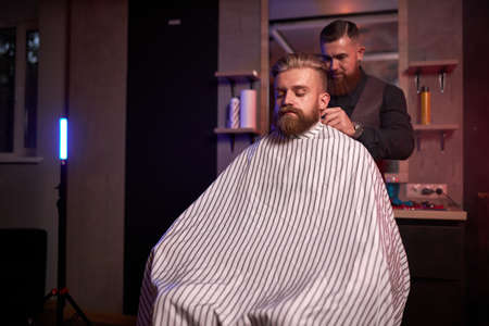 handsome caucasian man at the hairdresser in barber shop, barber male trimming hair to customer with electric razor at barbershop 版權商用圖片