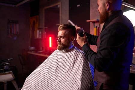 confident male hairstylist cut hair to elegant stylish man sitting in salon, young male enjoy the process of cutting 版權商用圖片