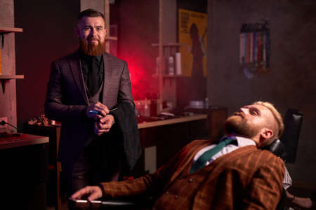 portrait of confident caucasian barber male and his client in salon, professional hair stylist going to cut bearded guy in suit, sitting on chair Archivio Fotografico