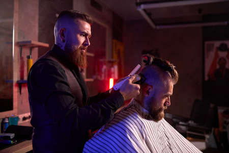 haircut at the hairdresser, in salon. barber male cuts the hair on the handsome young clients head, the process of creating hairstyles for men by professional