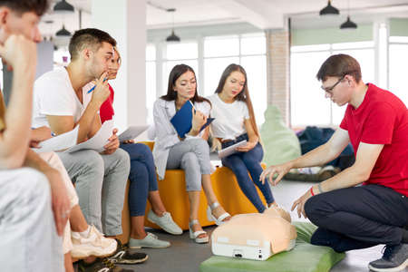 CPR class with male instructor speaking and demonstrating help, giving lessons of first aid. compression and resuscitation procedures. Cpr mannequin is used for an example 版權商用圖片