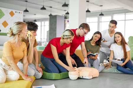 CPR class with young caucasian instructors speaking and demonstrating help first aid, cpr mannequin on the floor