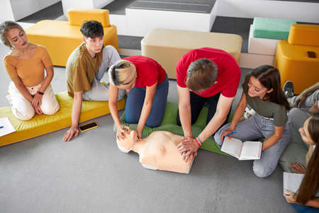 group of young diverse people practice first aid training by hand, first aid course in CPR dummy. concept of training skills to save lives, medicine