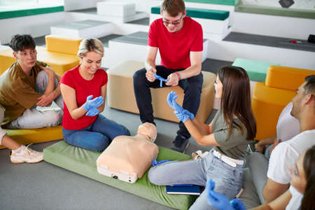 CPR class with male instructor speaking and demonstrating help, giving lessons of first aid. compression and resuscitation procedures. Cpr mannequin is used for an example Archivio Fotografico