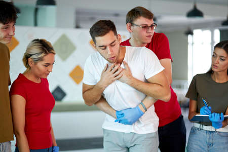 young man choking with male instructor standing behind performing heimlich maneuver indoors, group of people look at them