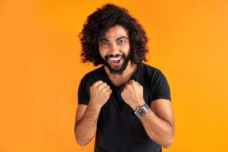 positive arabic curly man stand in boxer pose, ready to fight, play with someone, smile, orange background in studio