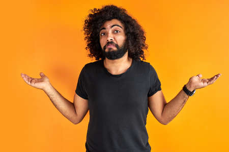 doubtful arab male is misunderstanding, show his incomprehension expression at camera, isolated over orange background